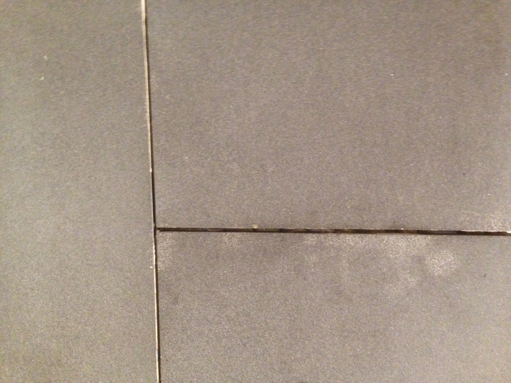 Unsealed honed basalt tile stained by mortar