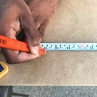 Kes measuring the cuts for our DIY mid-century desk