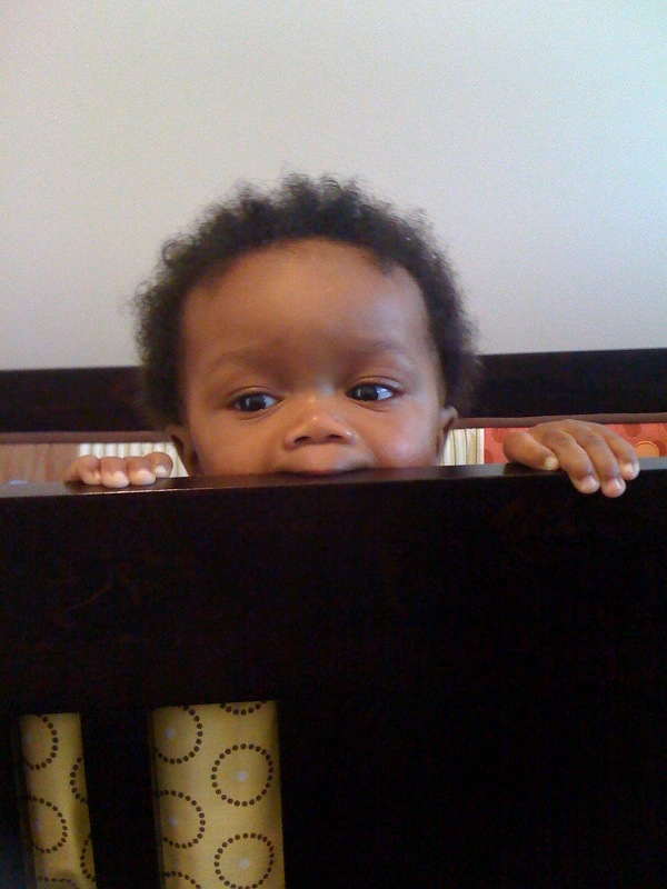 Baby Kash biting the side rail of his crib which is now the headboard of his double bed.