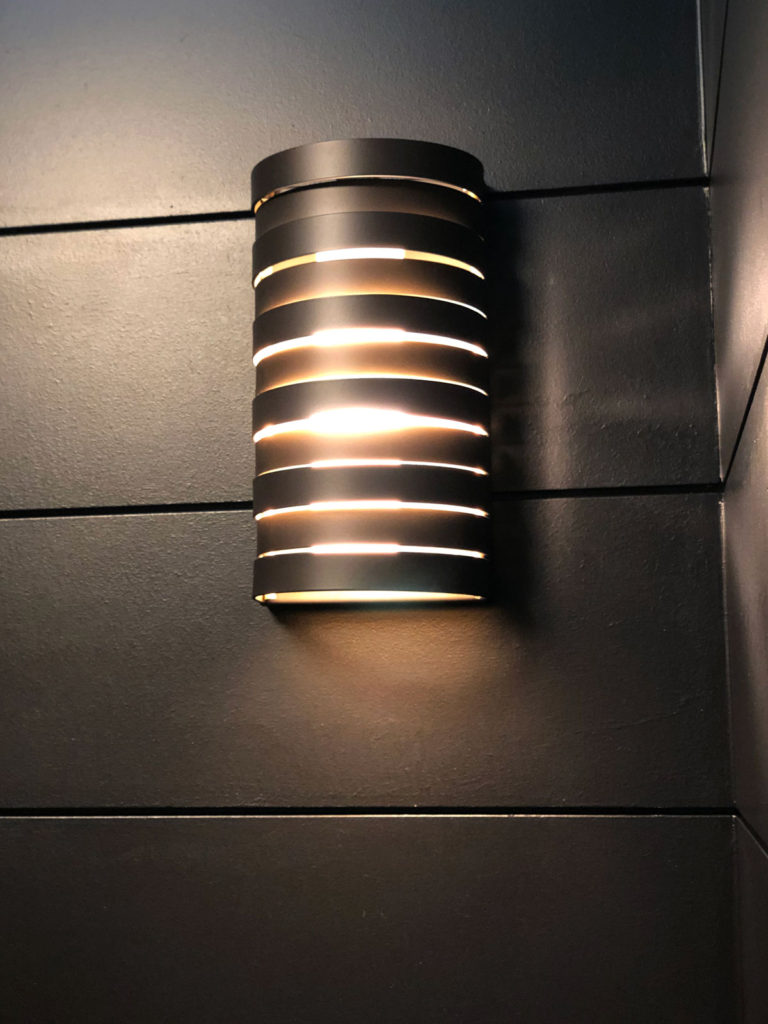 Paint & lighting makes all the difference. This Kichler Roswell wall sconce against the black shiplap walls create a sleek & striking ambiance to the powder room.
