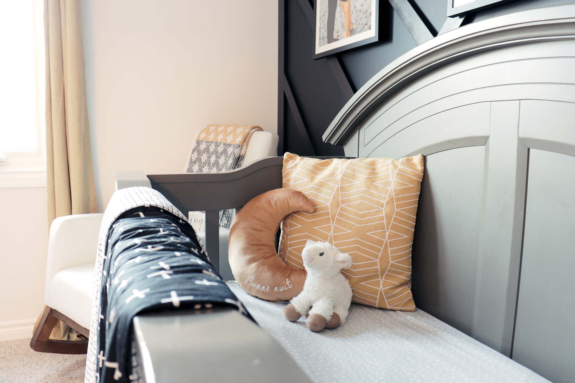 Geometric prints in the bedding and decor accents carry the theme and colour palette throughout the nursery design.