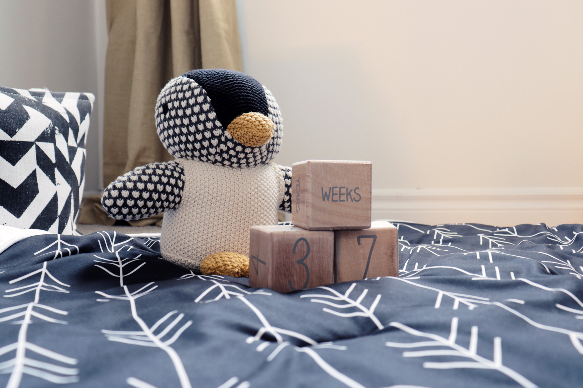 Crocheted penguin stuffed toy and wooden blocks counting the weeks until baby arrives.