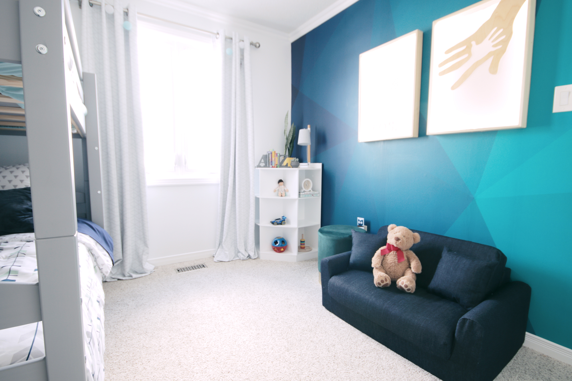 A bold wallpaper mural in jewel tone blues and greens add a fun pop of personality to the otherwise muted tones of this boys bedroom reveal.