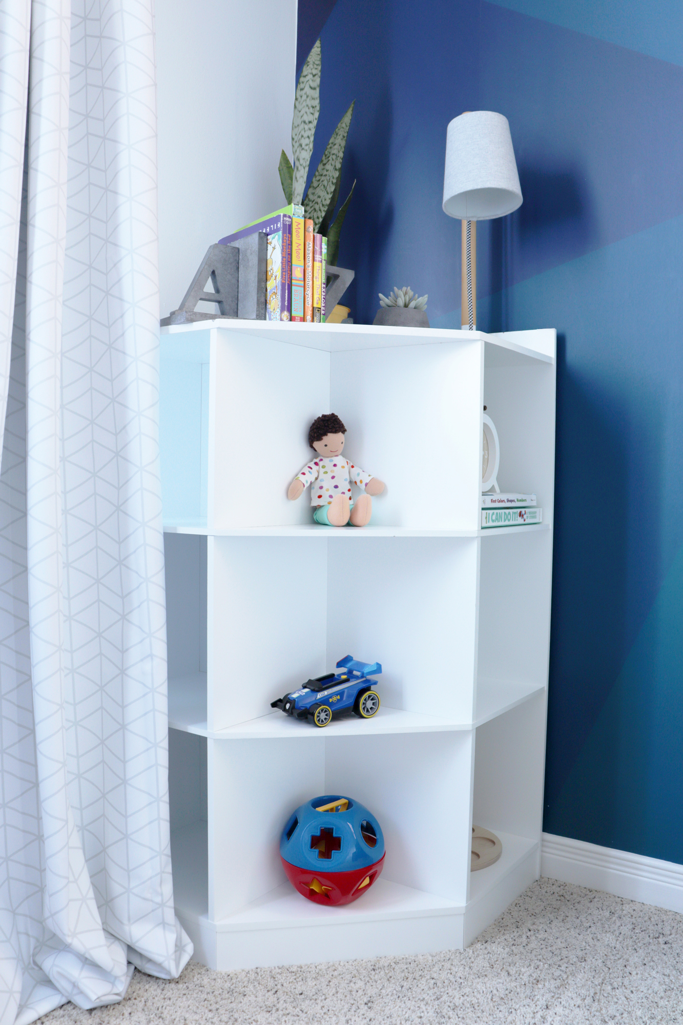 Corner shelf provides a cute storage solution for books, toys and other accents
